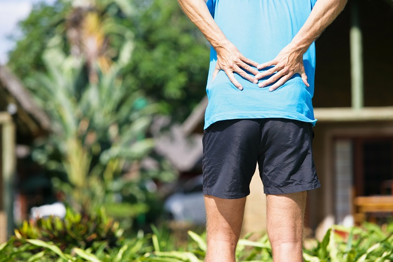 Man with low back pain holding lower back